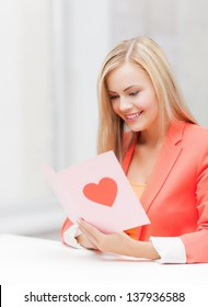 picture of woman holding postcard with heart shape.