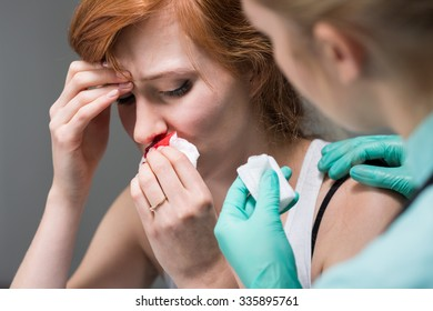 Picture of woman with nosebleed and nurse in hospital
