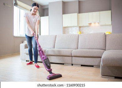 A picture of woman stands in studio apartment and cleaning the floor. She uses vacuum cleaner for that. Girl is looking down.