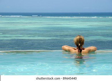 Picture of a woman in swimming-pool watching ocean
