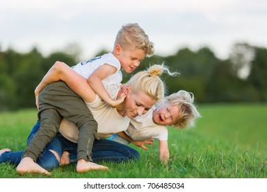 picture of a woman who romps with her two sons on the grass