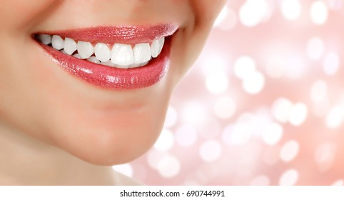 Picture of woman's smile against an abstract background with blurred lights