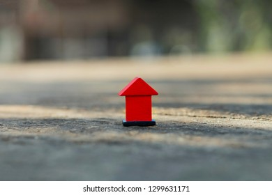 The picture of a wooden house model that is a toy made of bright red wood placed on a blurred background cement flo