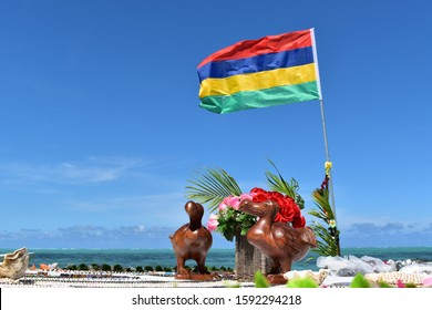 Picture of a wooden statue representing the symbol of Mauritius the Dodo bird. Mauritius flag in background.