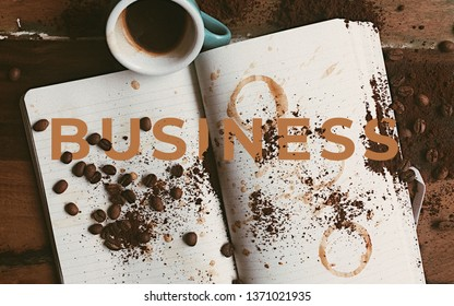 A picture of word business with a note book and a cup of coffee.