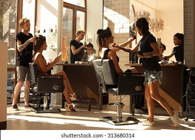 Picture of working day inside the beauty- sit on two chairs clients beautiful young girls. Hairdresser makes hair styling or hair cut, make-up artist doing make-up in a beauty salon- stock photo.