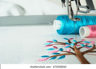 Picture of workspace in the embroidery machine close up look under the needle, lovely tree minimal style on background have two colorful thread cyan and pink.