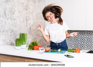 Picture of young amazing emotional woman dancing in kitchen indoors at home listening music with headphones cooking.