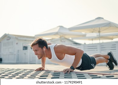 Picture of a young athletic man doing push ups, leg over leg listening music outdoors. Strength and motivation.