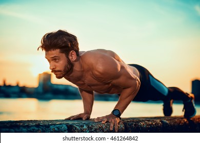 Picture of a young athletic man doing push ups outdoors.