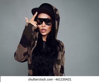 picture of a young attractive girl model with the Asian appearance in a baseball cap, sunglasses and camouflage jacket corrects forefinger cap