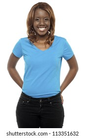 Picture of a young black woman posing in casuals. Smiling at camera