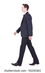 picture of a young business man walking forward - side view