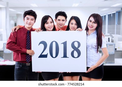Picture of young business people showing a board with number 2018 while standing in the office