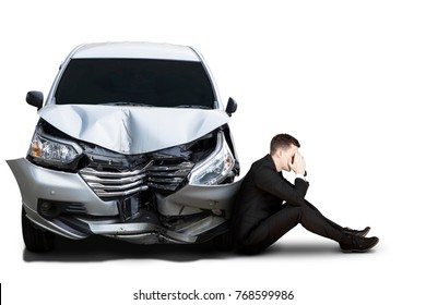 Picture of young businessman looks frustrated while sitting near a damaged car, isolated on white background