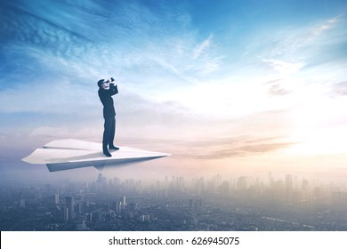 Picture of a young businessman standing on a paper plane while flying above a city and looking through a binoculars