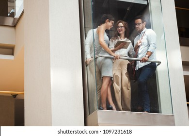 Picture of young businesspeople talking in elevator