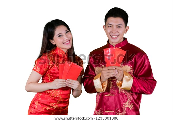 Picture of a young Chinese couple wearing cheongsam clothes and holding envelopes in the studio, isolated on white background