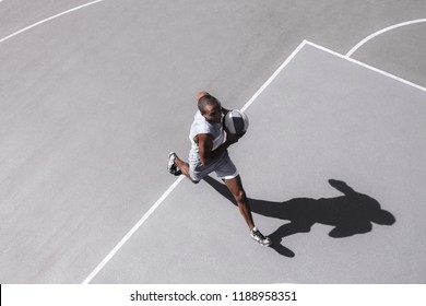Picture of young confused african basketball player practicing outdoor. Fit afro man in motion and movement. athletic and sport lifestyle concept. Top view
