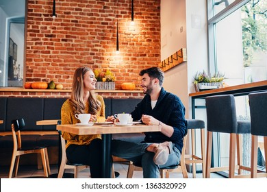 Picture of young couple dating at cafe. Young woman and man at coffee shop.