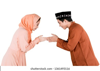 Picture of young couple giving greets hand to forgive each other while celebrating Eid Mubarak in the studio