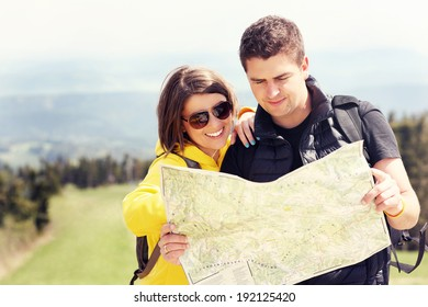A picture of a young couple with a map in the mountains in Poland
