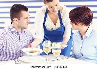 A picture of a young couple sitting in a restaurant and being served