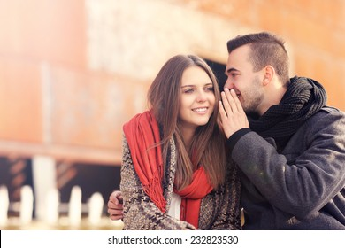 a picture of a young couple whispering on an autumn day