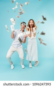 Picture of young emotional screaming caucasian loving couple isolated over blue background over money.