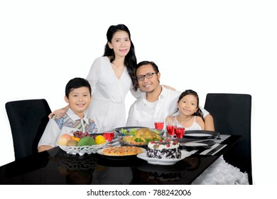 Picture of young family looks happy while having dinner together, isolated on white background