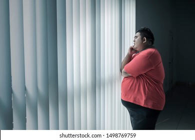 Picture of young fat man thinking something while looking out the window