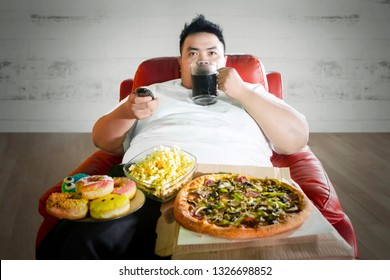 Picture of a young fat man watching television while enjoying junk foods and cola on the sofa. Shot at home