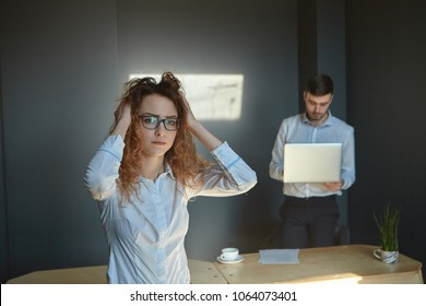Picture of young female manager in glasses touching her wavy hair while feeling stressed because she made mistake in financial report, her serious male boss standing with laptop in background