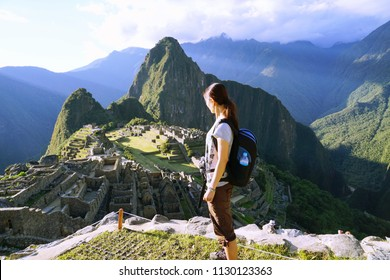 The picture of young female traveller standing at the cliff with the background of Machupicchu, Cusco, Peru. The capital city of Inca kingdom.