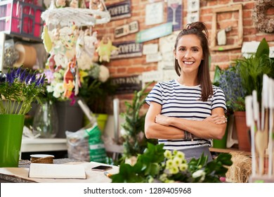 Picture of young florist standing in her shop and smiling at camera