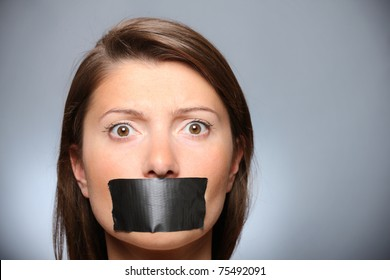 A picture of a young girl with her lips covered by a tape over grey background