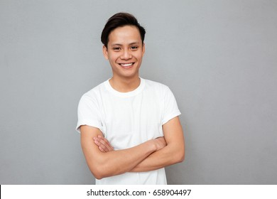 Picture of young happy asian man standing with arms crossed over grey wall. Looking at camera.