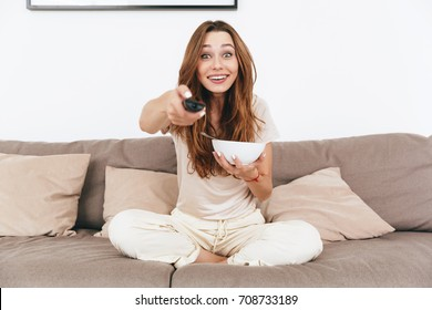 Picture of young happy emotional amazing pretty lady sitting on sofa indoors. Looking camera eating corn flakes watch TV.