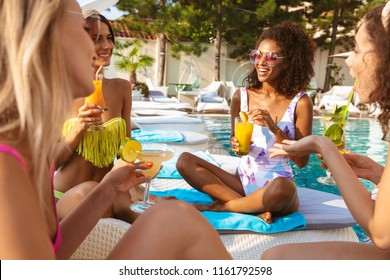 Picture of young happy emotional group of women friends sitting outdoors in pool dressed in swimwears talking with each other drinking cocktails.