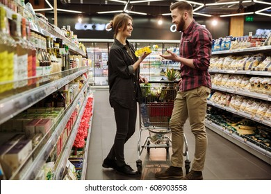 Picture of young happy loving couple in supermarket with shopping trolley choosing products. Looking aside.