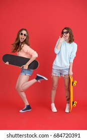Picture of young happy two ladies friends standing isolated over red background. Looking at camera holding skateboards.