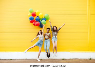 Picture of young happy women friends standing over yellow wall. Have fun with balloons.