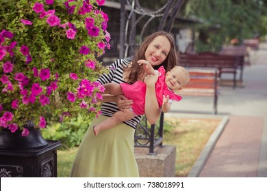 Picture of young lady brunette mother in soft zebra shirt and ivory colour skirt happy playing with baby daughter on city streets park close to pink rose flowers summer time child.
