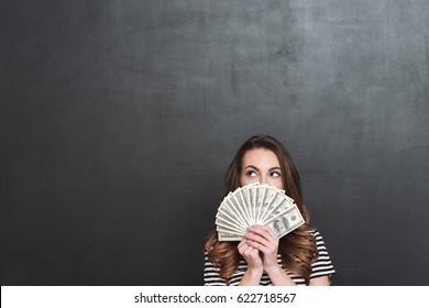 Picture of young lady standing over grey wall and holding money in hands. Looking aside.
