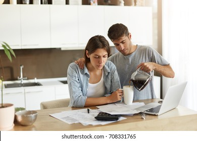Picture of young male and female doing paperwork together at home: serious wife sitting at dining table with papers and laptop computer, calculating bills while her husband serving coffee to her