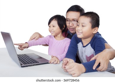 Picture of a young male teacher and two cheerful children using laptop together on the table, isolated on white background