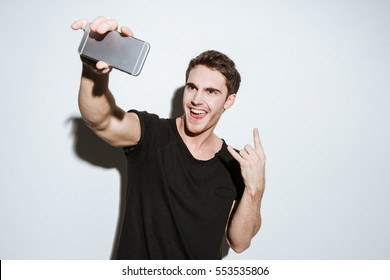 Picture of young man dressed in black t-shirt posing over white background and make a selfie by phone. Looking at phone.
