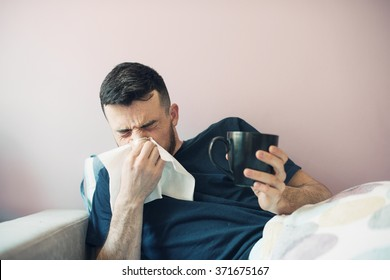 picture from a young man with handkerchief. Sick guy  has runny nose. man makes a cure for the common cold. The patient lies in bed