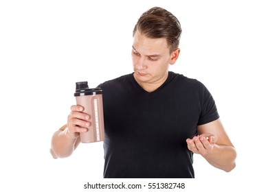 Picture of a young man holding a protein shake and some growth pills - isolated