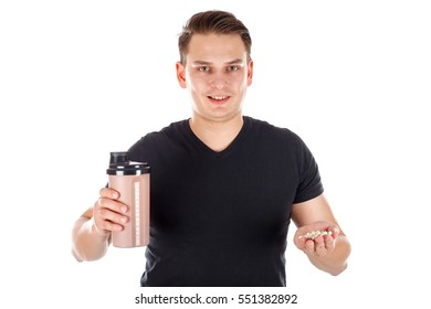 Picture of a young man holding a protein shake and some growth pills - isolated background